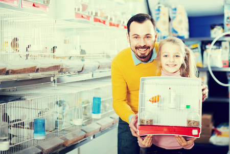 Young man and his daughter bought a cage for your pet canaries in the store Stock Photo