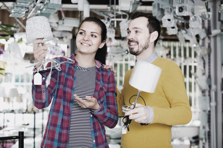 brightness: happy man and girl in lighter shop discussing purchase of bedside lamp for house Stock Photo
