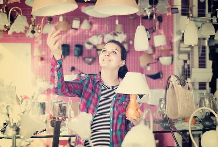 matt: Young spanish girl in lighter shop choosing  modern glass chandelier for house interior Stock Photo