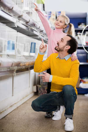 buying time: Smiling man and daughter deciding on best bird to keep in pet shop