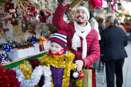 Happy father and child at counter with Christmas gifts in Christmas market