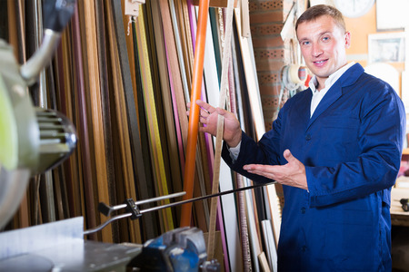 cheerful male seller standing in picture framing studio with wooden details