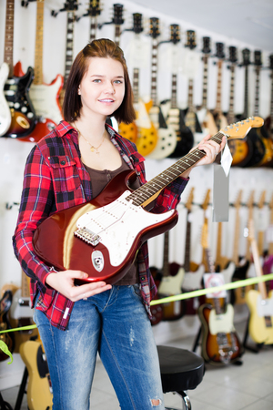 Smiling customer deciding on suitable amp in guitar shop