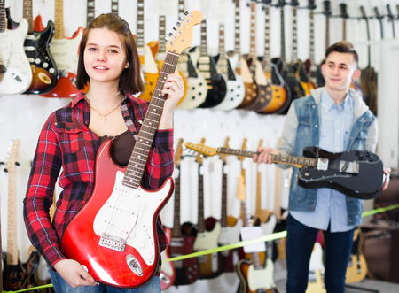 amp: Young buyers are deciding on suitable amp in guitar shop.