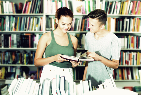 Portrait beautiful teenager girl and boy holding open textbook in hands in book store