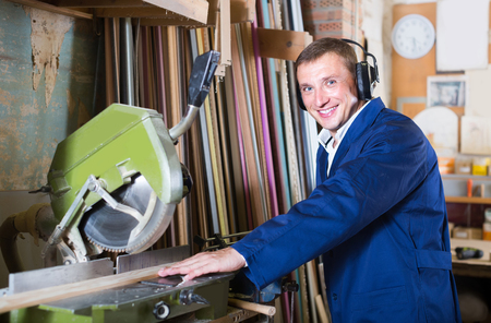 portrait of happy american  man in uniform working on electrical rotary saw indoors