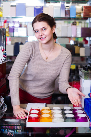 Young girl seller is displaying assortment in cosmetics shop.