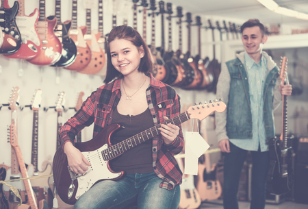 amp: Teenage visitors are deciding on suitable amp in guitar shop.