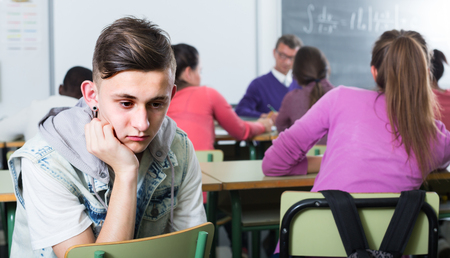 ?school pupil sitting away from classmates and feeling depressed Archivio Fotografico