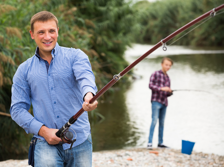 Excited adult man fishing on freshwater lake from shore