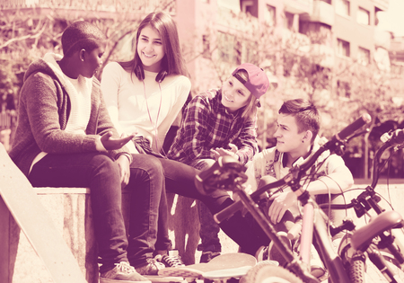 blabbing: positive girl and three happy boys hanging out outdoors and discussing something