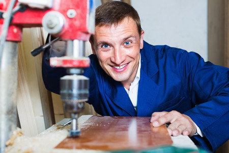 Smiling diligent man wearing protective workwear operating automatic screwdriver in wood workshop Stock Photo
