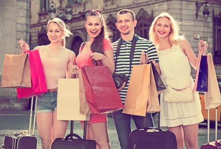 holiday spending: Portrait of three young smiling positive girls and one cheerful man standing with shopping bags outdoors