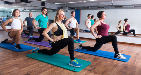 Young positive men and women exercising in dance hall Stock Photo