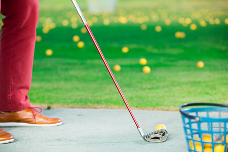 propel: Golfer ready to strike the ball with a club on the golf course Stock Photo