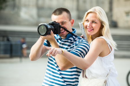 Two cheerful tourists holding camera in hands and photographing in city Stock Photo