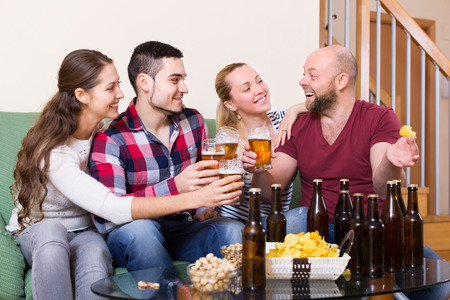 Cheerful happy young adults drinking beer and laughing at home