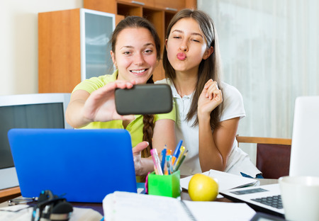 Student girls sitting at the table and making photo on the mobile phone