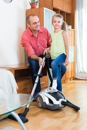 sweeper: Smiling father teaching little daughter vacuuming during clean-up at home Stock Photo