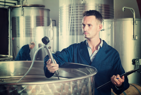 young professional man working in secondary fermenting section on winery and taking notes
