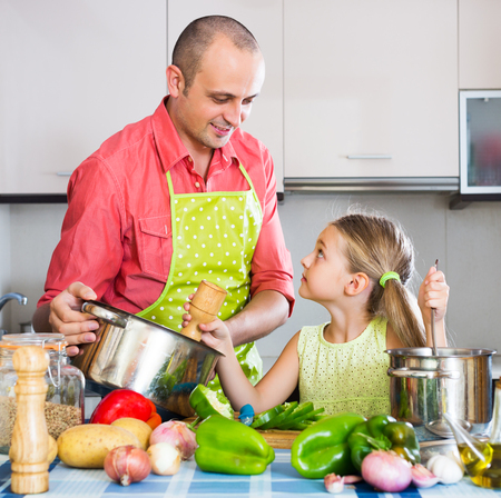 Portrait of smiling dad and little daughter cooking in kitchen