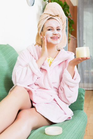 25s: Happy beauty girl lying on couch with cream over face indoors