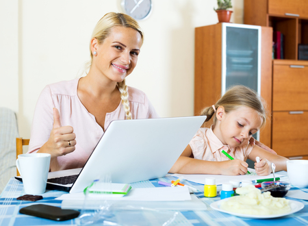 25s: Beautiful mother with daughter working from home using laptop. Focus on the woman Stock Photo