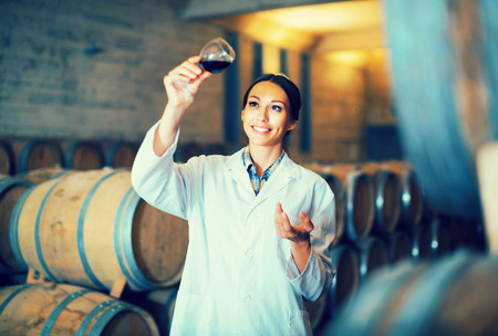 portrait of smiling young woman expert looking at wine sample in glass in cellar with woods Stock Photo