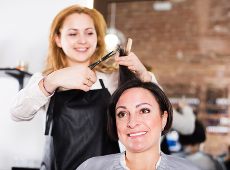 Young hairdresser doing fashionable hairdo to adult woman with scissors and combs in hairdress salon Stock Photo