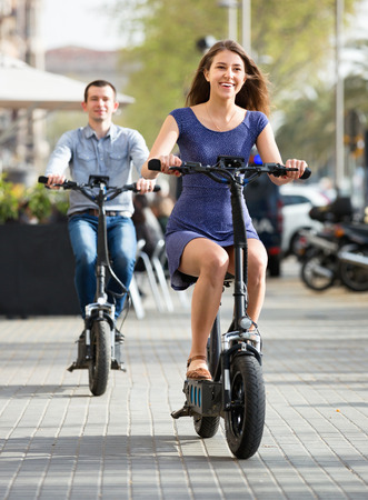 Happy pleasant smiling  man and woman with electrkc bikes in vacation on city street Stock Photo
