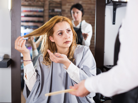 Young woman is dejected with work of hair stylist and her hairdo in hairdress salon