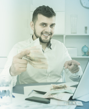 expertize: Smiling male manager earning money effectively online at home Stock Photo