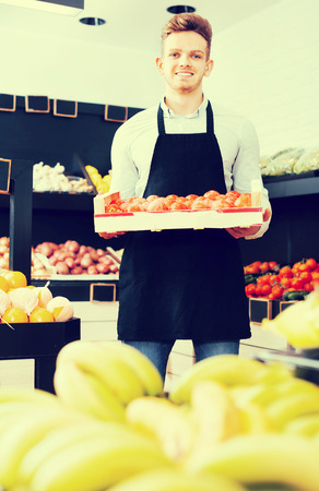 sorts: Young male seller carrying box of persimmons in the grocery shop