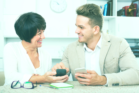 specifies: Smiling elderly mother with her young son studing new functions of smartphones