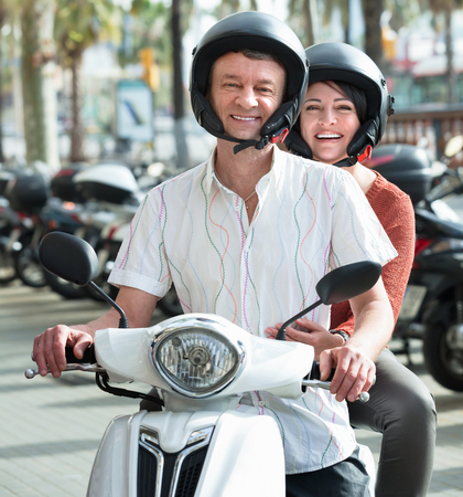Smiling happy adult couple sitting on a scooter in city street