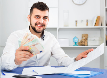 indebt: Young happy cheerful  man struggling to pay utility bills and rent for his apartment Stock Photo
