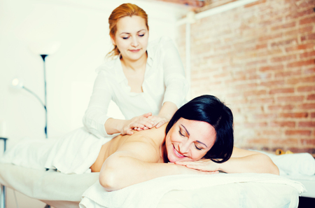 Young masseuse massaging shoulders and neck of adult woman in beauty parlor Stock Photo