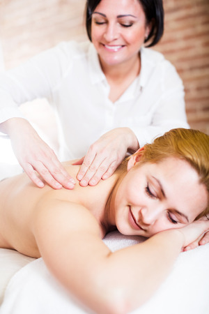 Adult masseuse softly massaging shoulders and neck of young woman in massage salon. Selective focus on hands