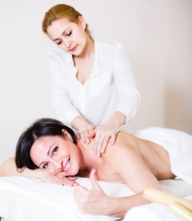 25s: Cheerful woman likes work of young masseur in spa salon and procedure of massage shoulder area
