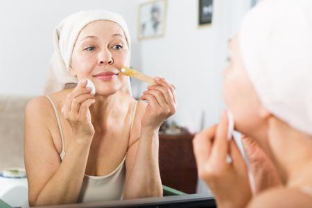 habitual: Senior woman starting body hair removal at home Stock Photo