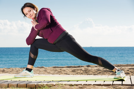 Positive girl exercising on exercise mat outdoor Stock Photo