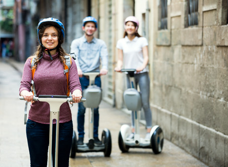 25s: Two smiling girls and guy traveling through city by segways Stock Photo