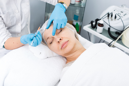 Woman doctor making beauty injection to aged female client