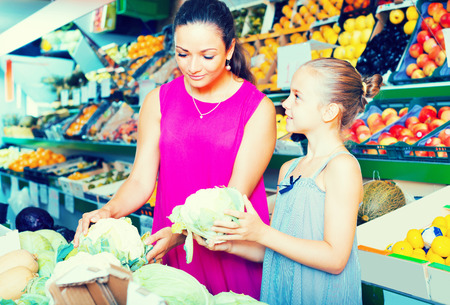positive young woman with girl buying cabbage on marketplace