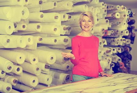 boastful: Senior smiling female customer boasting purchased home textiles in textile shop Stock Photo