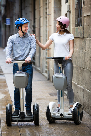 25s: Happy young man and woman 20s traveling through city by segways