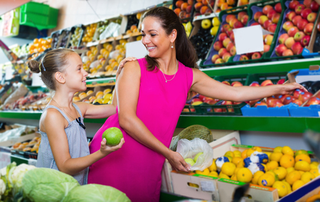 Female with daughter buying fresh apples in fruit section in grocery shop