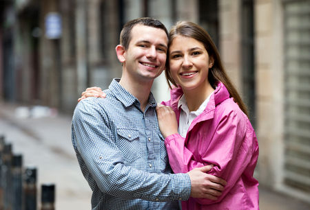 Portrait of happy man and girl loving each other on city street