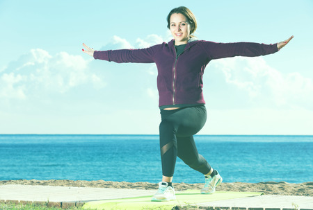 Pretty girl exercising on exercise mat outdoor Stock Photo