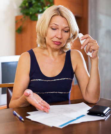 Portrait of sad mature woman reading documents at the table in home or office